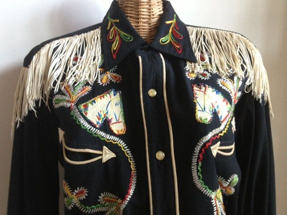 Incredible 1950s HBarC genuine gaberdine riding shirt with white fringe all the way around. Double rainbow stitched horse heads, arrow front pockets and embroidered pockets. Fringe is supposed to flow as you ride  No flaws other than a small bit of wear to the ends of the cuff, otherwise looks to be barely worn.  Measures 20 inches pit to pit and 30.5 collar to tail. Marked as a large but these were always custom tailored so use the measurements.    No international shipping.