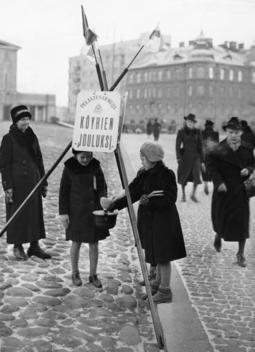 Tyttö laittaa rahaa pelastusarmeijan joulupataan 1938. Kuva: Troberg Eero. Vapriikin kuva-arkisto.
