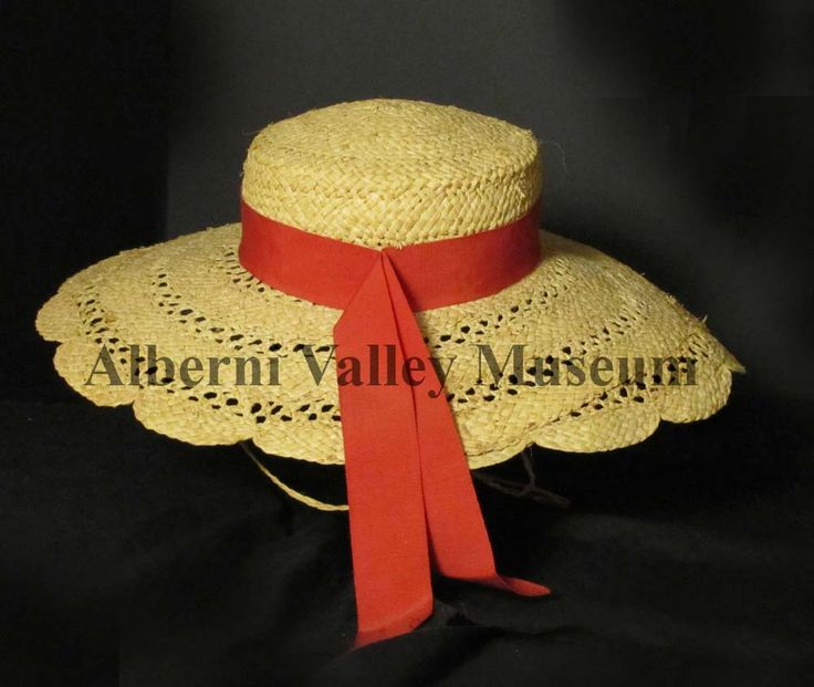 Large straw hat has a deep crown, a wide brim with scalloped edge, and a red grosgrain ribbon, 1920-1940. During the 1920s and 1930s, accessories were an integral part of a woman's wardrobe. Summer hats, especially during the 1930s, were large, wide- brimmed and trimmed with flowers, ribbons and osprey feathers.  [Alberni Valley Museum Collection 1971.84.1h]