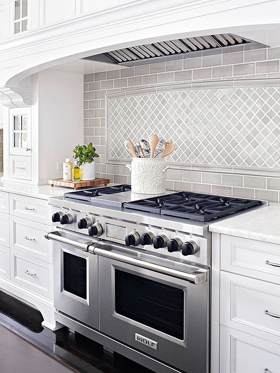 This kitchen is simple and symmetric with its neutral color palette and congruent cabinetry. A gray ceramic-tile backsplash matches the room's color scheme and style, but an eye-catching inset above the range instantly adds a visual interest on a long wall. The angled tiles are framed with a slightly arched top, drawing attention to the space while still aligning with the kitchen's style.