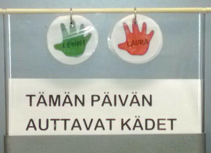 Järjestäjät eli auttavat kädet. Oppilaiden nimet on kirjoitettu käsiin ja uusi auttava käsi löytyy kun päällimmäinen käsi siirretään takimmaiseksi. Pojat vihreällä ja tytöt punaisella.