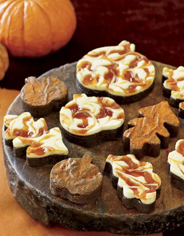 Cheesecake Brownies - Topped with cream cheese frosting and swirls of pumpkin butter, these are no ordinary brownies. Cut into autumn shapes, such as pumpkins and leaves, and then arranged on an antique cutting board, these brownies make a scrumptious display. Read more: Fall Dessert Recipes - Halloween Party Treats - Country Living