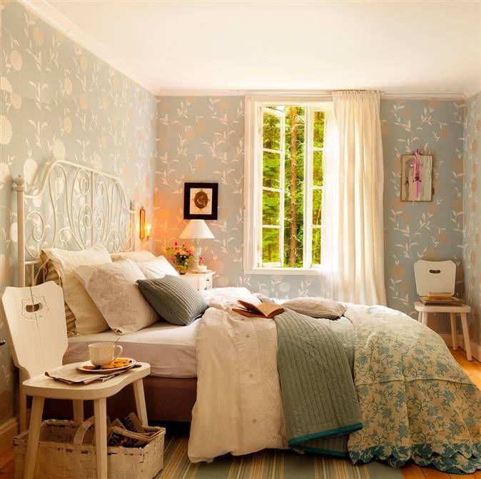 Dormitorio con cama de metal y pared con papel pintado en azul y muebles en blanco