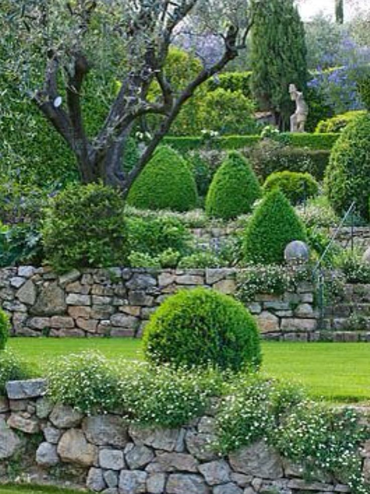 Formal Mediterranean Garden With Stacked Fieldstone Walls, Boxwood  Topiaries, And Statuary.