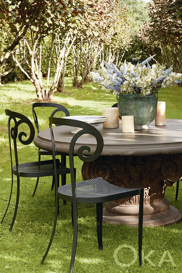 With a magnificent sculptural pedestal base reminiscent of a Corinthian capital, this round outdoor table from OKA is a practical and artful addition to any garden.