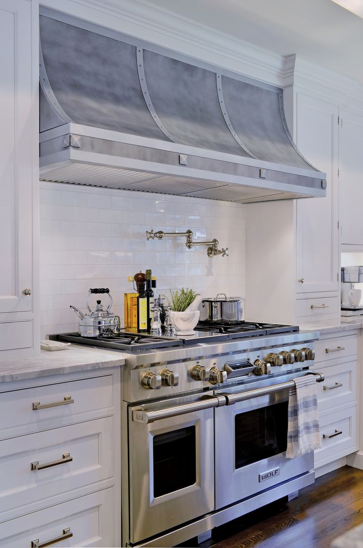 The six-burner Wolf range with double ovens is any cook's dream. It is topped off with a customized hood range with a unique nailhead detail designed by Showcase Kitchens. Design elements were selected by Sabrina Simon. Timeless white subway tile is used throughout for the backsplash and allows the cooking area to be the focal point.