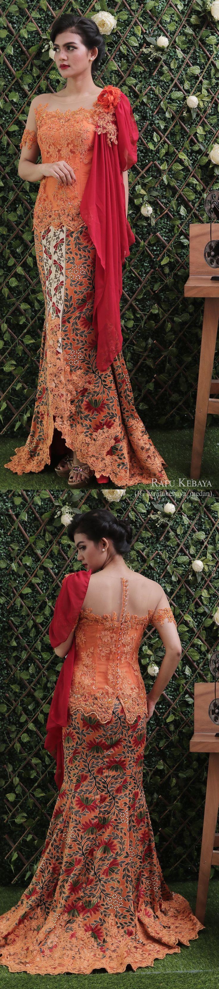 Kebaya orange dengan aplikasi bunga bahu dan rok batik bordir (IG @ratukebaya_medan)