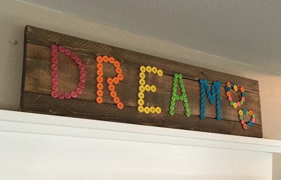 This Dream sign made with buttons measures about 24 x 5.5. The sign is stained in jacobean. Adorable sign for kids playrooms, bedrooms, nurseries, and classrooms. Comes complete with Sawtooth hanging hardware. My pieces may be made from wood that has some flaws or imperfections, but it just adds to the character of the wood! Each piece is handmade at time of purchase so each sign may vary slightly from the exact one shown in the listing photo.  Need something a little different? Message me…