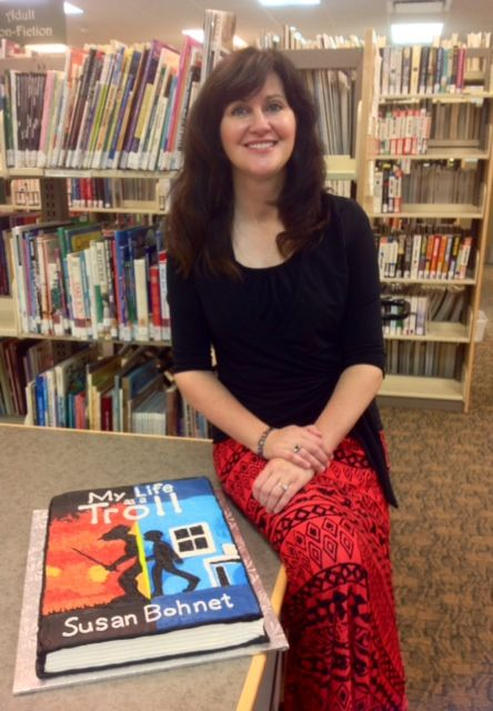 """Susan Bohnet book launch of """"MY LIFE AS A TROLL, October 23, 2014 at Claresholm library. Susan is seen here sitting next to the cake made in the image of the book's cover."""