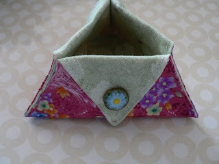 Triangular Thread Catcher Tutorial from Needling Things Blog.  This is SO simple - just 2 triangles of fabric, a little bit of sewing and 3 cute buttons.  Could make it any size you wanted.  I would also consider doing some decorative stitching for the top-stitching instead of just a straight stitch.
