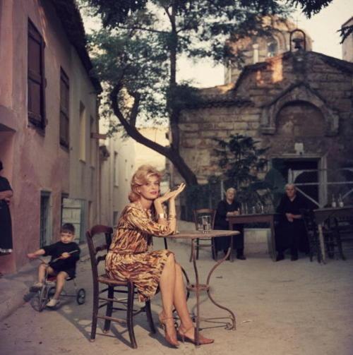 "Slim Aarons. ""Greek actress Melina Mercouri sitting at a street cafe in Athens"". 1961. Monastiraki, Athens, Attica, Greece."