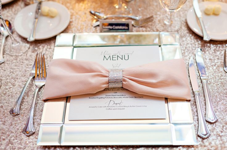 Light pink dinner napkins were held together by sparkling napkin rings and situated atop square, mirrored charger plates. #placesetting Photography: Kristen Weaver Photography Read More: http://www.insideweddings.com/weddings/elegant-summer-wedding-with-timeless-color-palette-in-orlando-fl/630/