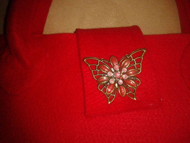 Borsa in feltro rosso con chiusura magnetica, sovrastata da farfalla in filigrana d'ottone dipinta a mano