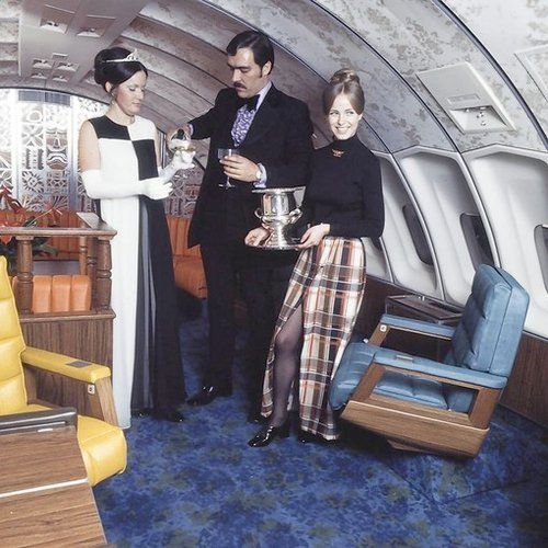 "The upper deck lounge on a United Airlines 747 in 1972. ~ so much going on.  The tiara, ugly blue carpeting, walnut stained wood accents, ruffled lavender tuxedo shirt, and the ""sexy"" plaid maxi skirt. LOL"