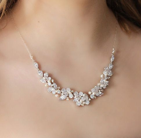 This statement bridal necklace is made with Rhinestones, natural freshwater pearls, and Swarovski crystals. It is finished with a sterling