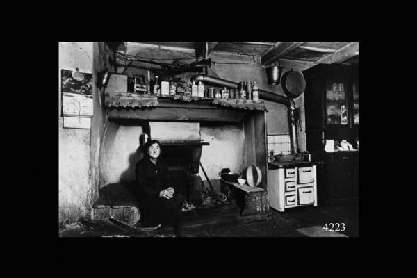 Cucina all'interno di una casa contadina con anziana donna seduta davanti al camino.