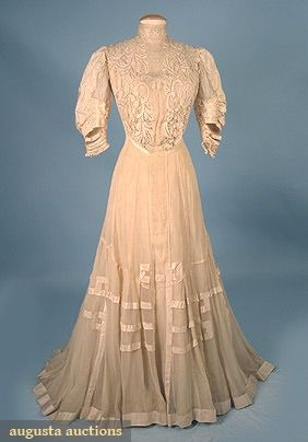 "SILK & LACE TEA GOWN, c. 1908 1-piece cream silk chiffon & silk taffeta trained gown, bodice decorated w/ hand made silk bobbin lace, B 39"", W 25"", front L 60"", back L 66"", (silk missing between taffeta cuff bands, scattered small spots, lining shredded) excellent."