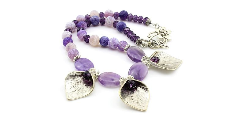 """A gorgeous 20"""" frosted Agate gemstone necklace with 3 tulip flowers as the focal point. Each tulip has a purple faceted crystal set within. Enhanced with oval Agate gemstones, purple faceted crystals, and finished using a beautiful flower toggle clasp."""