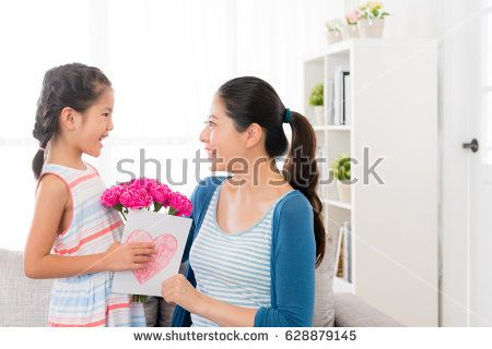 smiling little girl prepare a pink carnation bouquet and love card giving gift for beautiful mom at mother's day at home in the living room sofa looking each other.