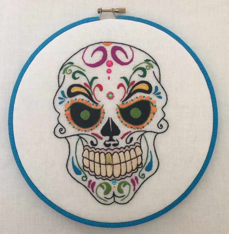 """Mr. Evil Sugarskull Dia De Los Muertos Hand Embroidered Hoop Art. Mr. Evil colorful sugar skull 8"""" hand embroidered hoop art. This piece is done on fine white linen, for a nice glowing look. I also used metallic gold thread for the one gold tooth. Embroidered with a variety of quality threads & stitches. This skull is embellished with sequence for a 3 dimensional effect. The hoop is wrapped in a sparkly blue ribbon and then finished off in the back with a pretty fabric and cording. Easy…"""
