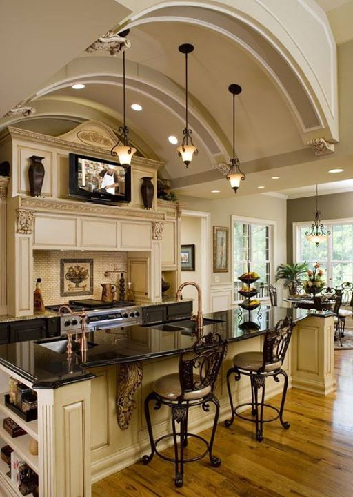 I love this kitchen - the cream colored cabinets with the black countertop and chairs - just so pretty. I also love the idea of a fireplace in the kitchen.