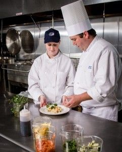 Photo of culinary school chef and student in commercial kitchen. Industrial photography by Nashua, NH commercial photographer Dan Splaine. …