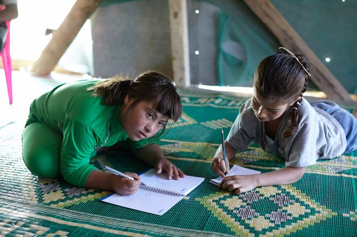 Eight-year-old Aya, right, dreams of becoming a doctor one day, but since becoming a refugee has not been able to attend school. She and her sister Labiba, 11, who has disabilities, write in notebooks in their family's home in an informal settlement in Dalhamiyeh in the Bekaa Valley, Lebanon. http://rfg.ee/rh5I4