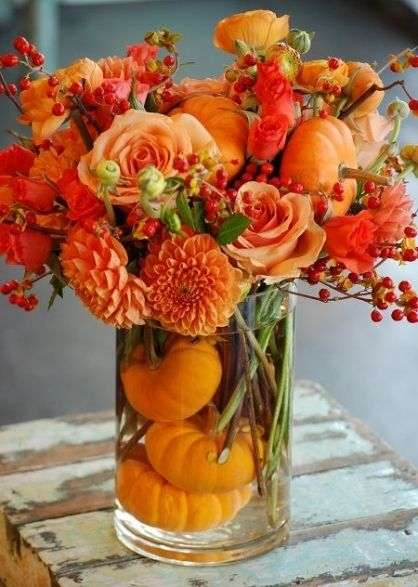 vase of orange dahlias, bittersweet and an accent of pumpkins at the base as the centerpiece