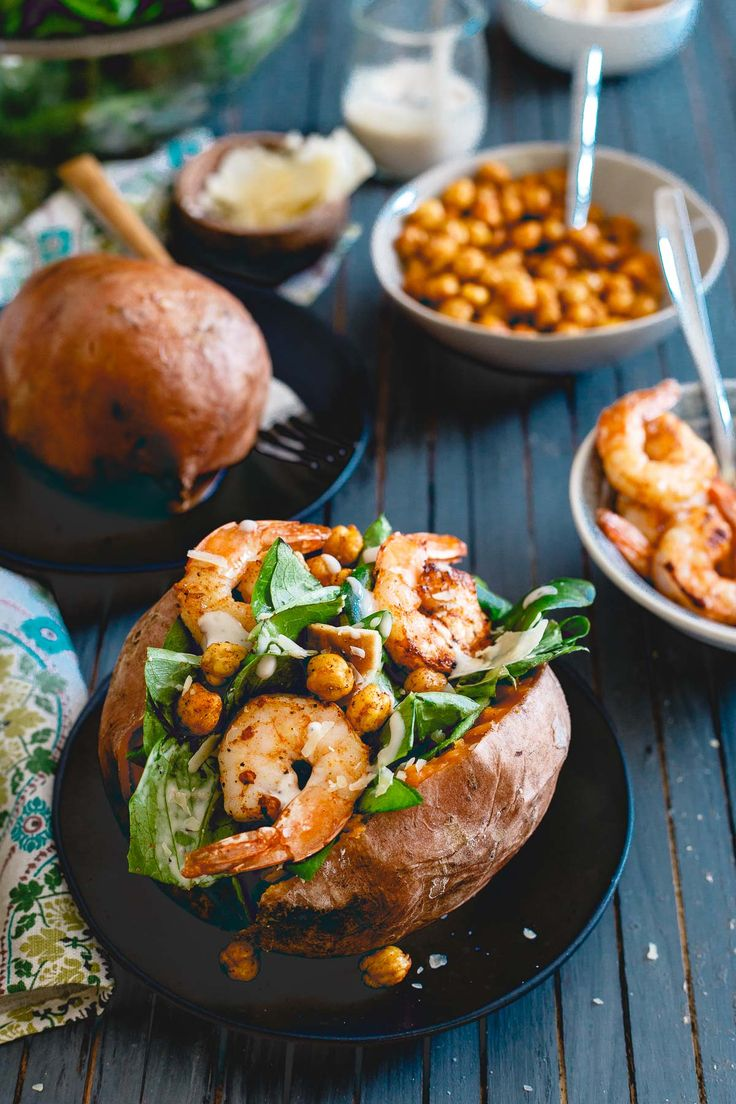 Ad: Topped with spicy cooked shrimp and roasted chickpeas, these caesar salad stuffed sweet potatoes are a healthy, complete meal!