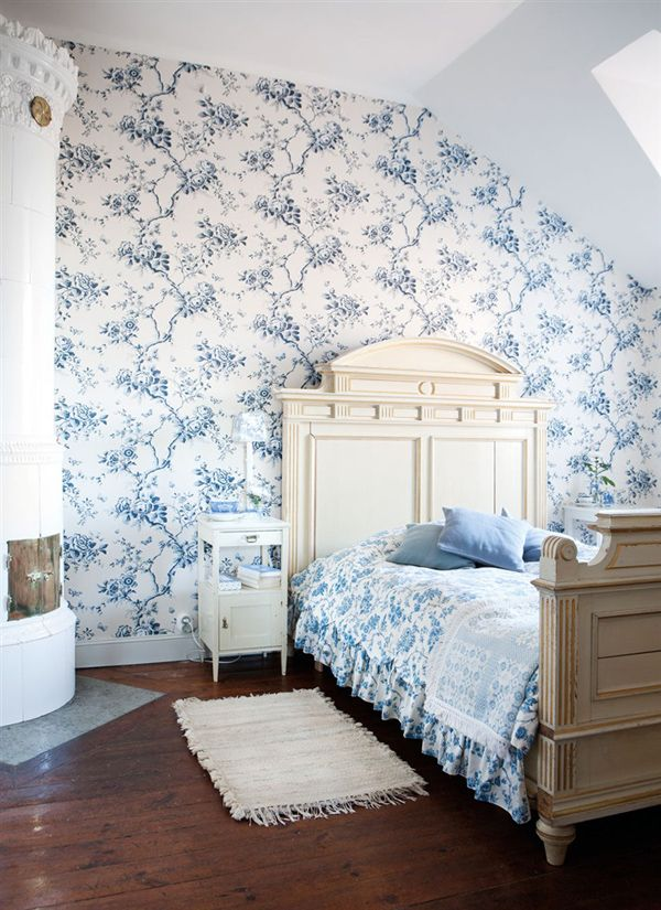 a classic toile in a Swedish bedroom with a tiled stove