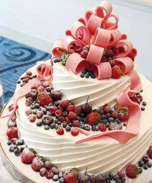 ベリーのウェディングケーキ イチゴとラズベリーをふんだんにつかったケーキ。チョコレートでできたピンクの大きなリボンが可愛らしい仕上がりになっています。
