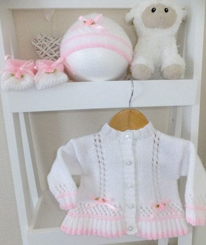 Beautiful girls cardigan with matching hat & shoes, all trimmed with pink satin ribbon and rose buds I have this one in stock 3-6 months Available to order in sizes 0-3 months - 3-6 months & 6-9 months any colour combination you would like Hand knitted in a pet and smoke free home using