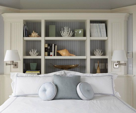 Bookcase headboard outfitted with white wainscoting and readling light sconces- WANT.