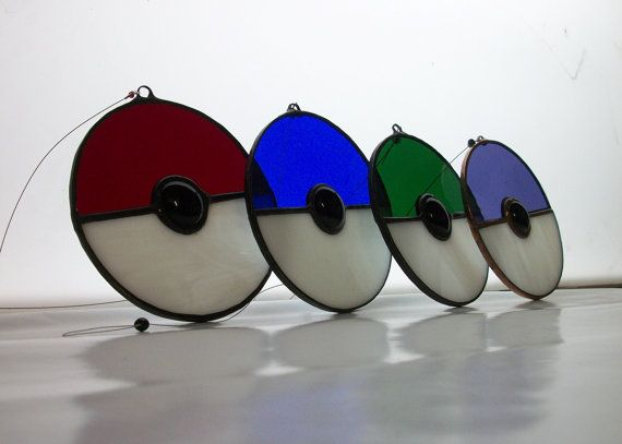 Stained Glass Pokeball suncatcher, inspired by the popular video game Pokémon. Catch one, or catch em all!  Approx. 3.5 x 3.5, and available in 4 color options: Starter Red, Blue, & Green with black patina; and Master Purple with copper patina. Strung with 7-strand .30mil wire, ready to hang.     Handmade in the USA by a Tiffany Certified, Arizona-based glass shop specializing in original and recycled glass art inspired by popular themes from the entertainment, comic and gaming industry…