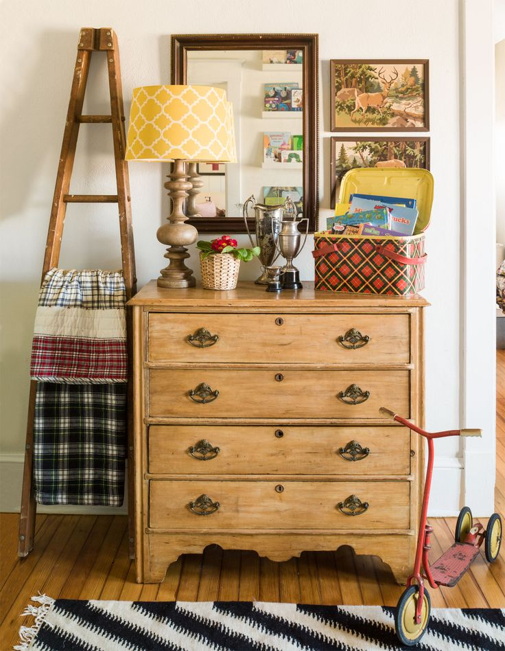 """I'm a big fan of bringing outdoor pieces inside,"" says Trinity. This rough-hewn ladder was once used at an apple orchard but now offers up a quaint spot to store extra blankets in her son Knox's nursery. Retro, charming, and easy to find (a quick Etsy search will yield more than 7,000 results), this 1950s paint-by-number art is Trinity's go-to for instant wall interest. The weathered red vintage scooter inspired the palette for Knox's room. ""I love decor that also has a function. It won't…"