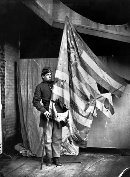 A Union soldier holding the tattered flag of the Eighth PA Infantry during the American Civil War. USA 1864.