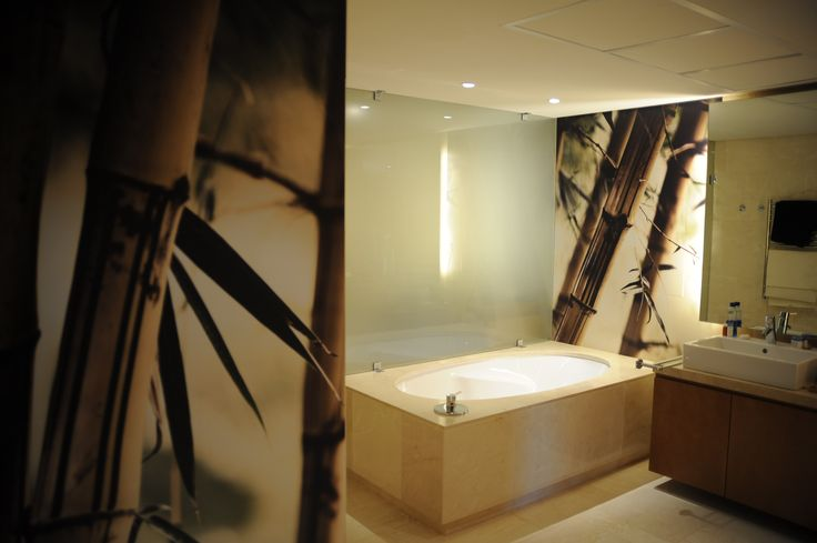 This bathroom for Jacob Wiese is given a placid feel owing to the bamboo wallpaper used behind the bath.