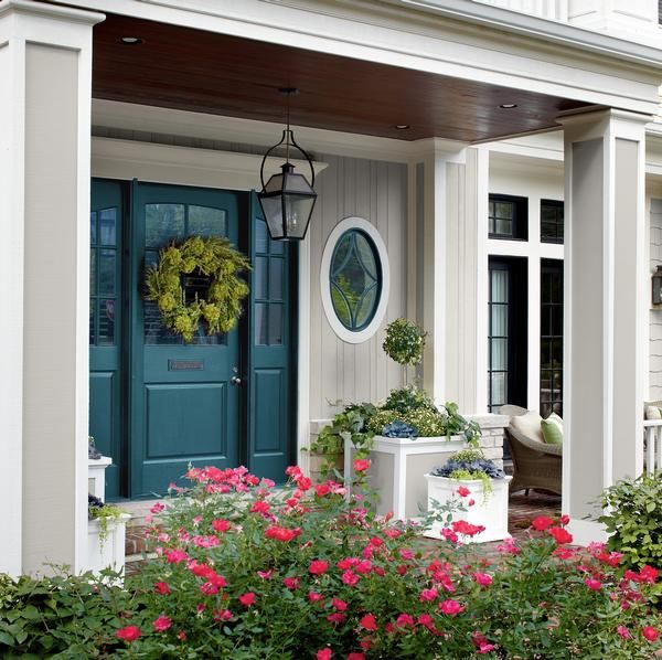 Against a background of pale gray and white trim, an intense shade of teal on the front door, the sidelights and the window trim sings.