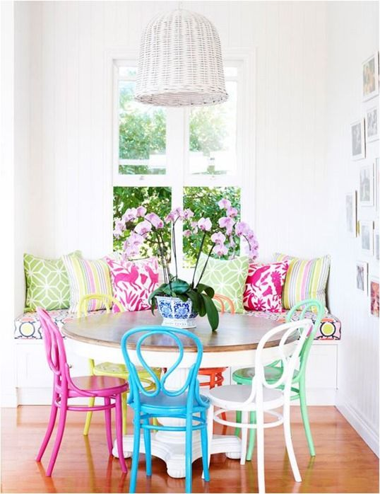 Love the colors! Mix-matched, brightly colored chairs in the dining nook.
