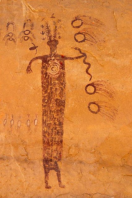 Meteor Shaman, San Rafael Swell, SE Utah; photo by John Mumaw.[Pictograph depicts a shaman holding a snake as spirit images fly about. JE]