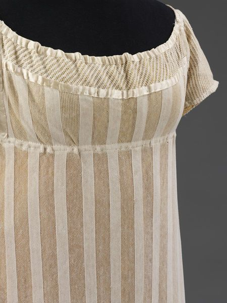 """Dress, ca. 1812, England. Victoria and Albert Museum: """"Dress made of warp-knitted fabric, probably cotton. With a pattern of alternating stripes of close plain knitting and open work. The sleeves and a band inserted around the neck are also in knitted cotton with a smaller pattern of alternating plain and open work."""" (Click through for more pictures.)"""