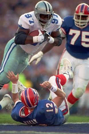 Dallas Cowboys defensive end Jimmie Jones flies over Buffalo Bills quarterback Jim Kelly for a touchdown after recovering Kelly's fumble in the first quarter of Super Bowl XXVII.