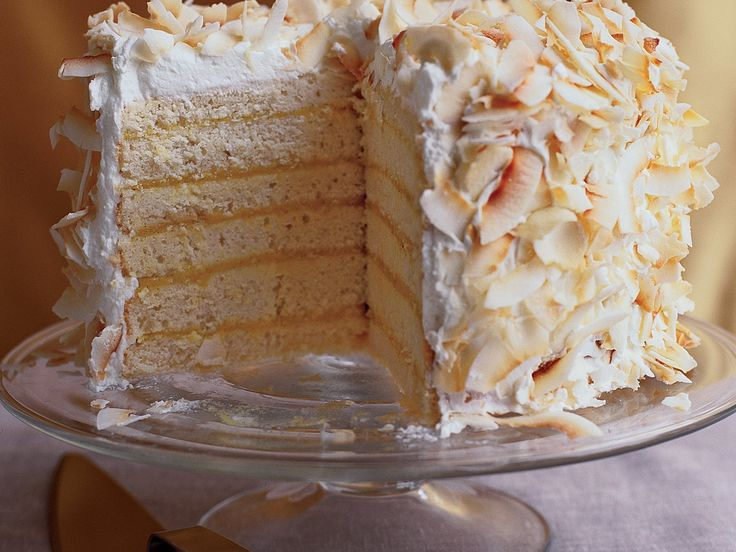 Six-Layer Coconut Cake with Passion Fruit Filling | This towering coconut cake is made up of super-moist coconut cake layers spread with tangy passion fruit curd, then topped with whipped cream and toasted coconut.