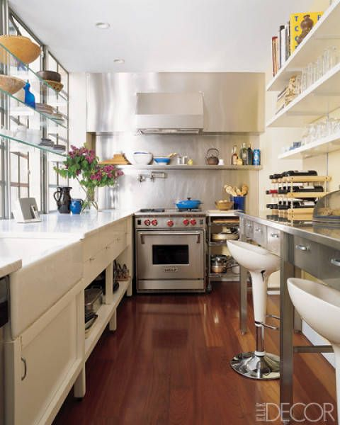 The kitchen of a Manhattan townhouse designed by Temple St. Clair Carr features Carrara-marble counters and a custom-made stainless-steel hood and storage unit; the stove is by Wolf.   - ELLEDecor.com