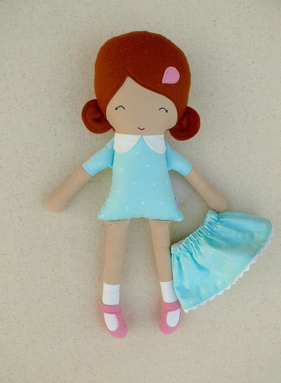 This is a small handmade cloth doll measuring 15 inches. She is wearing a sweet, aqua polka dotted dress with a matching, removable skirt, white socks, and pink maryjanes. Her cinnamon-red hair is worn in low, rounded ponytails and accented with a matching, pink, felt barrette. She is made from 100% cotton fabrics, wool blend felt, and polyester fiberfill. Her seams are triple stitched, and she is firmly stuffed with fiberfill. Please hand wash only. Lay flat to dry. Thank you for viewing…