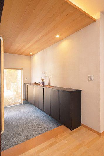 6.天然木の天井からもれる光、銀ねず色の珪藻土を塗った壁、豆砂利洗い出しの床が印象的な玄関。横長のシューズクロークは大容量。