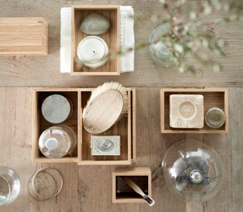 Kasser af bambus i forskellige størrelser fyldt med sæber, børster og en tandbørste, set ovenfra.