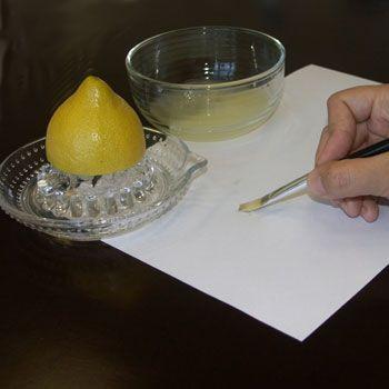 Hand malt mit Pinsel Zitronensaft auf Papier