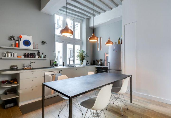 Cucina dalle dimensioni compatte disegnata da Tatiana Nicol privilegiando linee semplici e funzionalità. Le pareti, in quest'area dell'appartamento parigino, sono di un grigio tenue, come a definire lo spazio