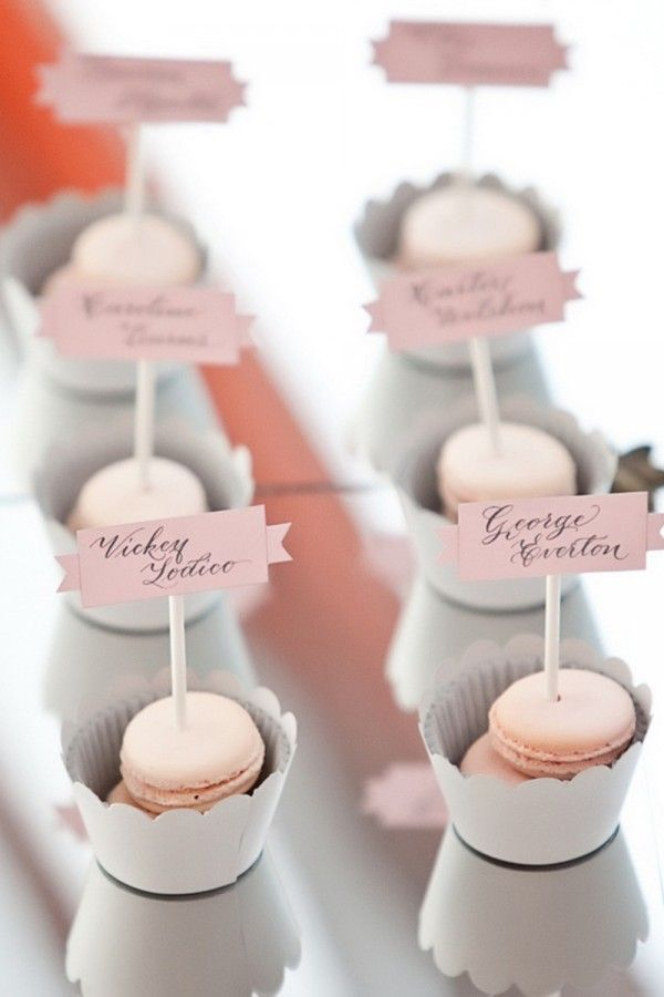 Can totally DIY this - except for the macarons =( Escort Cards -- IN THE CUPCAKES?!?   mini cookie sandwichs?